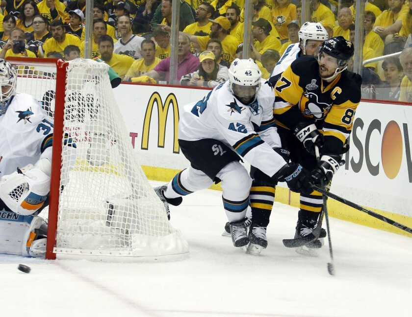 Pittsburgh Penguins' Sidney Crosby, right, centers the puck past San Jose Sharks' Joel Ward (42) as Sharks goalie Martin Jones (31), defends during the first period in Game 1 of the Stanley Cup final series Monday, May 30, 2016, in Pittsburgh. (AP Photo/Keith Srakocic)