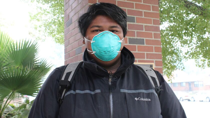 Sisco Martinez of Sacramento wears his N95 mask after picking one up from a local fire station. The
