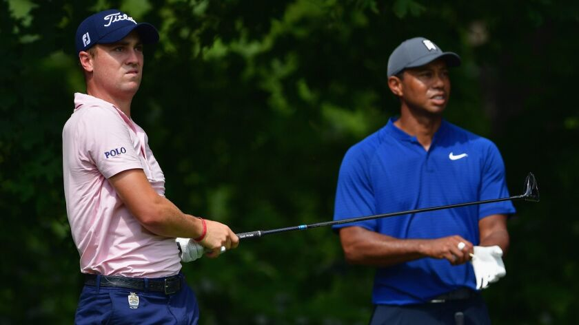 Justin Thomas plays a shot as Tiger Woods looks on during a practice round prior to the 2018 PGA Championship at Bellerive Country Club on Wednesday in St. Louis.