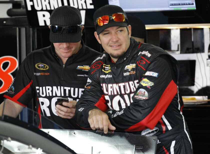 FILE - In this Thursday, May 21, 2015 file photo, Martin Truex Jr, right, looks out of the garage before practice for Sunday's NASCAR Coca-Cola 600 Sprint Cup series auto race at Charlotte Motor Speedway in Concord, N.C. With only three career wins in 368 races, Truex is the odd man in NASCAR's finale in south Florida on Sunday, Nov. 22, 2015. (AP Photo/Terry Renna, File)