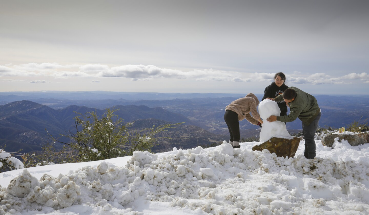 Overlooking the Pauma Valley, brother and sisters from San Marcos, Maria Calbillo, left, Anette Calbillo, center, and Fernando Calbillo, right, build a snowman in a snow covered turnout along East Grade Road on Palomar Mountain, November 30, 2019, in San Diego County.