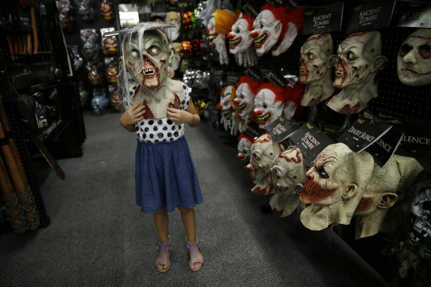 """In this Sept. 2, 2015 photo, six-year-old Olivia Vlaicu, of Maywood, N.J., tries on an """"ancient zombie"""" mask at the Spirit Halloween store, in Paramus, N.J. Spirit Halloween, a chain of more than 1,150 pop-up shops across the country, has reincarnated a former Staples store and filled it with 4,000 costumes and accessories with themes ranging from zombies to superheroes and princesses to prison inmates. (AP Photo/Mel Evans)"""