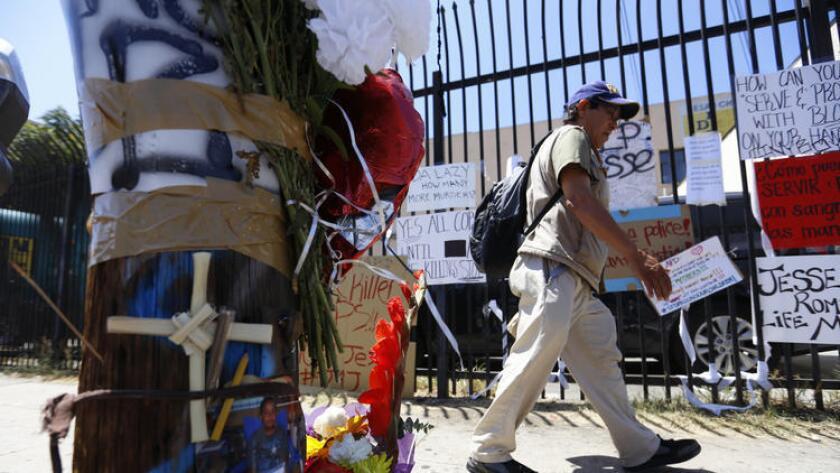 Un hombre pasa frente a cartels, flores y velas colocadas en el area de Boyle Heigts donde Jesse Romero, de 14 anos, murio a manos de agentes del LAPD.