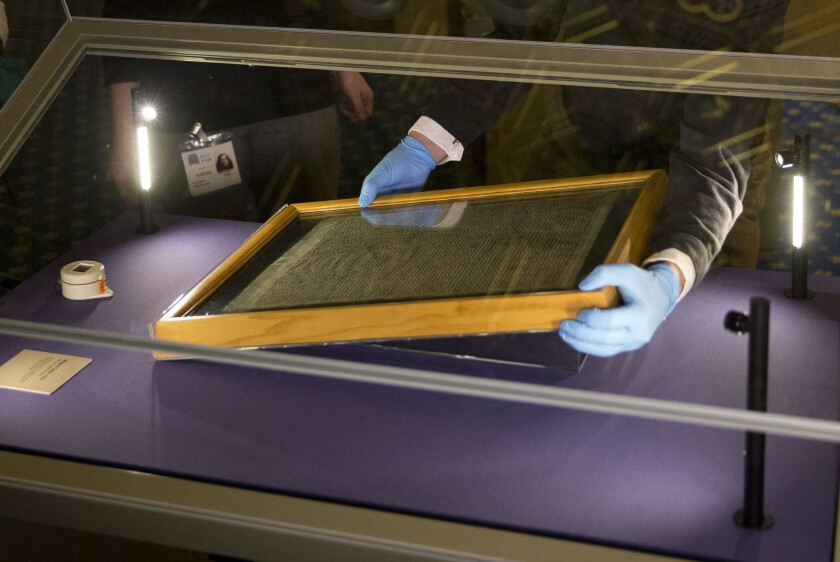 """FILE - In this Thursday, Feb. 5, 2015 file photo, the Salisbury Cathedral 1215 copy of the Magna Carta is installed in a glass display cabinet marking the 800th anniversary of the sealing of Magna Carta at Runnymede in 1215, in Salisbury, England. A judge has on Friday, July 10, 2020 sentenced a man to four years for attempting to steal Salisbury Cathedral's Magna Carta. Salisbury Crown Court Judge Richard Parkes sentenced Mark Royden, describing the failed theft as a """"determined attempt on a document of huge historical importance. (AP Photo/Matt Dunham, FILE)"""