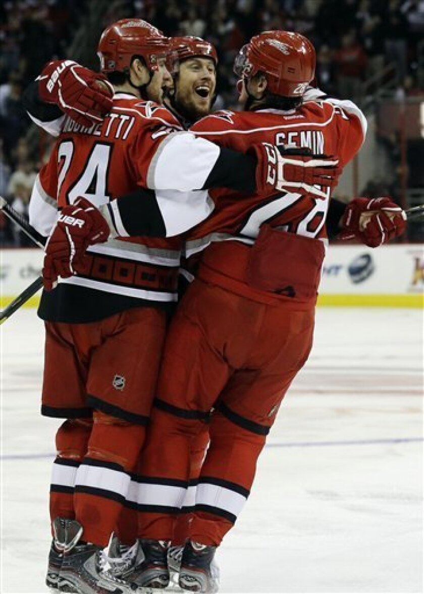 Carolina Hurricanes' Joe Corvo, center, celebrates his goal against the Toronto Maple Leafs with Bobby Sanguinetti (24) and Alexander Semin (28), of Russia, during the second period of an NHL hockey game in Raleigh, N.C., Thursday, Feb. 14, 2013. Carolina won 3-1. (AP Photo/Gerry Broome)