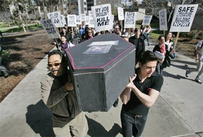 UCSD professor Takashi Fujitani, (left) graduate student L. Chase Smith and others marched yesterday to  protest what they call a hazardous work environment in the university's Literature Building. Since 2000, there  have been eight reports of breast cancer among women working in the building. (E