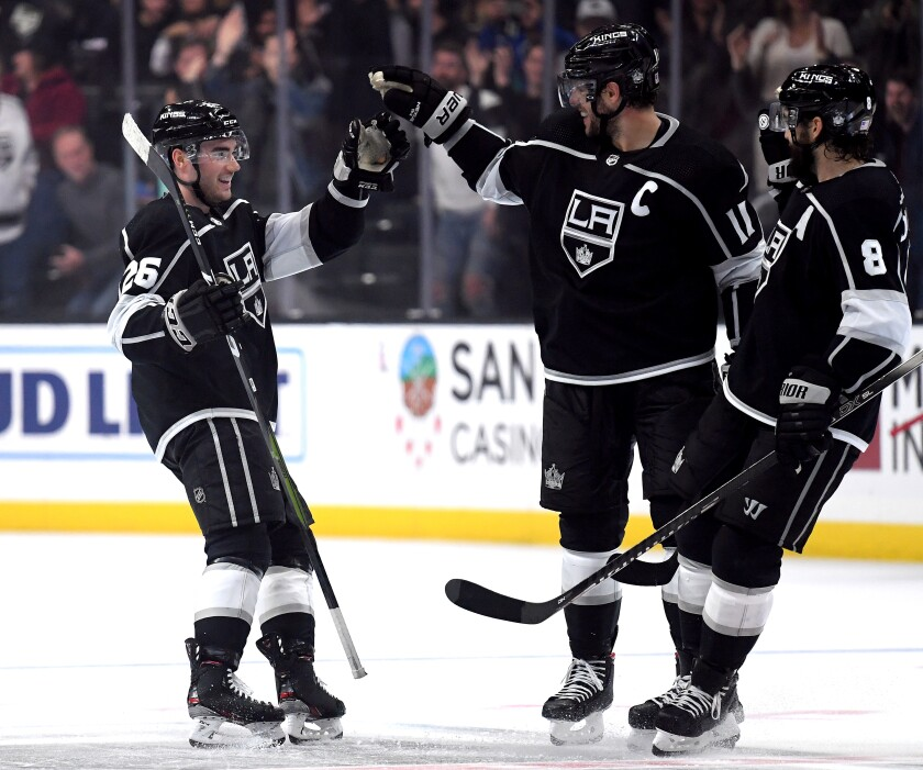 Kings rookie defenseman Sean Walker celebrates his empty goal with Anze Kopitar (11) and Drew Doughty (8) during the third period of a win Nov. 12 over the Wild.