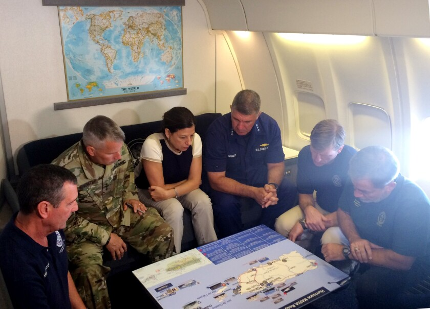 Acting Homeland Secretary Elaine Duke, center, is briefed on the Hurricane Maria response during a flight to Puerto Rico.