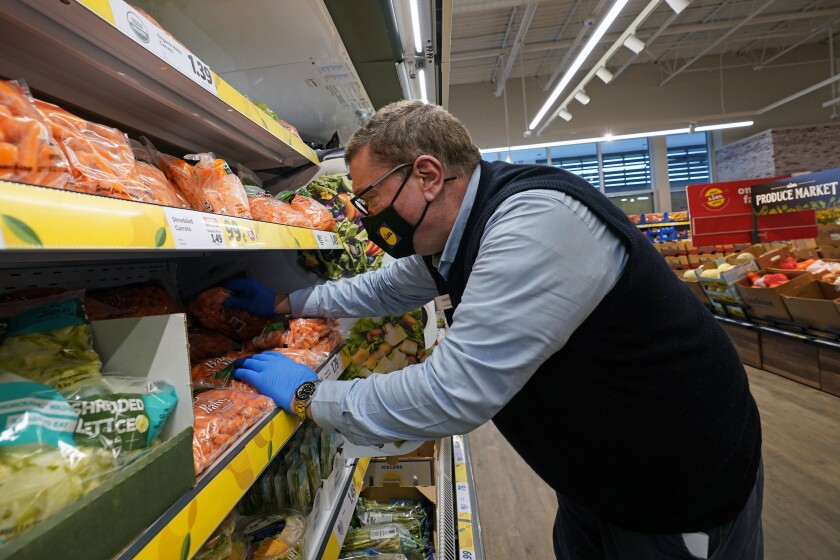 """In this Thursday, Feb. 4, 2021 photo, Joseph Lupo, an employee of the grocery chain Lidl, arranges carrots in the produce aisle at the grocery market where he works in Lake Grove, N.Y., after getting vaccinated against coronavirus earlier in the day. The German grocery chain is offering a $200 financial incentive all workers who get vaccinated against COVID-19. Lupo, a Lidl supervisor who fell ill with the virus in March, was elated to get his first vaccine dose. """"I never ever want to get COVID again, or see anybody else get it,"""" said Lupo, 59. (AP Photo/Kathy Willens)"""