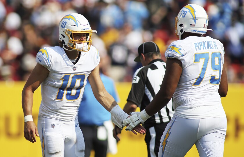 Chargers quarterback Justin Herbert and offensive tackle Trey Pipkins slap hands.