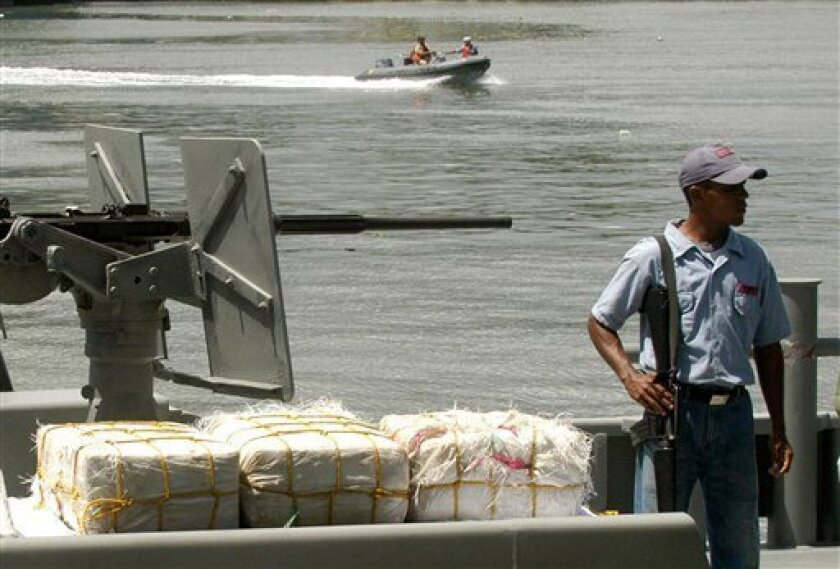 FILE - In this June 25, 2007 file photo, a Dominican Navy soldier stands guard over bales of cocaine during a news conference in Santo Domingo, Dominican Republic. Authorities in the Dominican Republic seized 9 tons of cocaine in 2012, the third consecutive record, according to the country's nation
