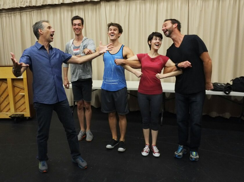 """Director-choreographer Roger Castellano, Stephen Petrovich (Scarecrow), Carson Twitchell (Tinman), Carlin Castellano (Dorothy) and Randall Dodge (Cowardly Lion) rehearse a scene from Moonlight Stage Productions' musical """"The Wizard of Oz."""""""