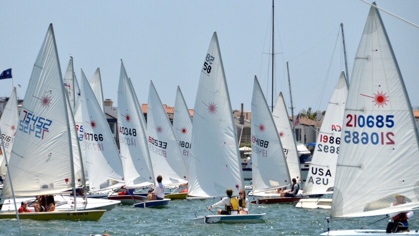 Lasers navigate into position at the start line of Flight of Newport Beach sailboat race in Newport Harbor on Sunday.