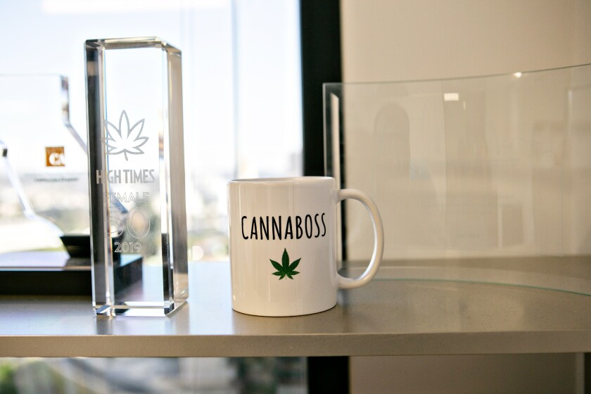 "A ""canniboss"" coffee mug in Cat Packer's office"