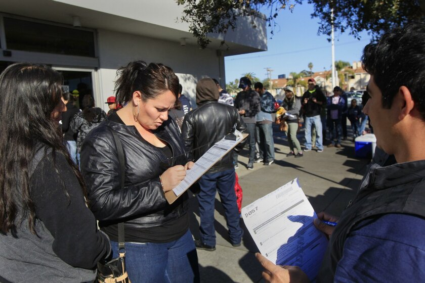 Aristea Merlo (with clipboard middle) fills out paper work as she waits for her appointment with Cristina Madrigal (left) and David Contreras (right) at the Department of Motor Vehicles in Hillcrest on Friday in San Diego, California. Today is the first day of the new law allowing undocumented immi