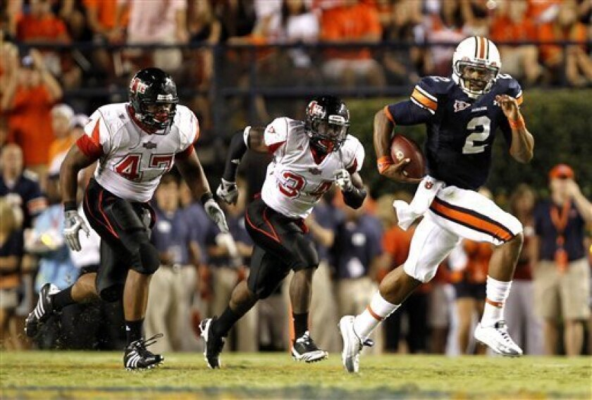 Auburn quarterback Cameron Newton (2) breaks for a 71-yard touchdown past Arkansas State defensive end Justin Robertson (47) and Najel Byrd (34) during an NCAA college football game on Saturday, Sept. 4, 2010, in Auburn, Ala. (AP Photo/ Butch Dill)
