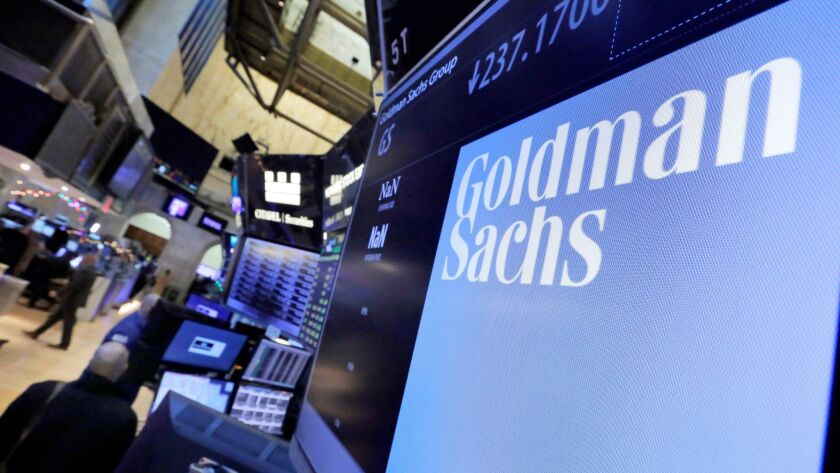 The logo for Goldman Sachs appears above a trading post on the floor of the New York Stock Exchange.