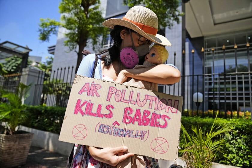 """Una activista muestra un cartel con una muñeca que representa a los bebés afectados por la contaminación aérea, durante una protesta ante la Corte del Distrito Central de Yakarta, donde se dirimía una demanda contra autoridades indonesias por no mejorar la calidad del aire, el 16 de septiembre de 2021. El cartel dice """"La polución aérea mata (especialmente) bebés"""". (AP Foto/Dita Alangkara)"""