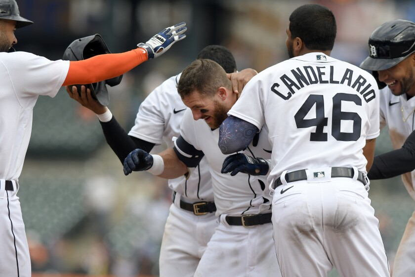 Detroit Tigers' Robbie Grossman, middle, is congratualted by teammates after walking in the winning run with the bases loaded against the Tampa Bay Rays in the eleventh inning of a baseball game, Sunday, Sept. 12, 2021, in Detroit. (AP Photo/Jose Juarez)