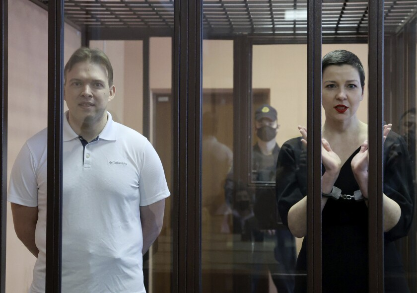 Maxim Znak and Maria Kolesnikova stand in a cage for defendants in court.