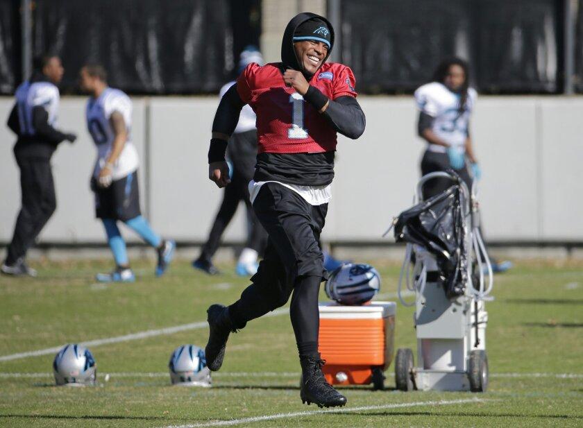 Carolina Panthers Cam Newton runs across the field before the NFL football team's practice in Charlotte, N.C., Tuesday, Nov. 24, 2015. (AP Photo/Chuck Burton)