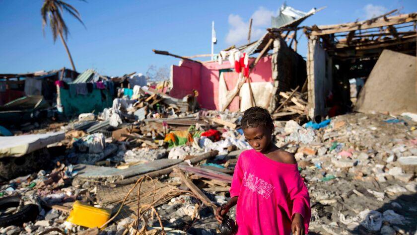 A girl as she walks through debris where homes once stood after Hurricane Matthew hit Jeremie, Haiti.