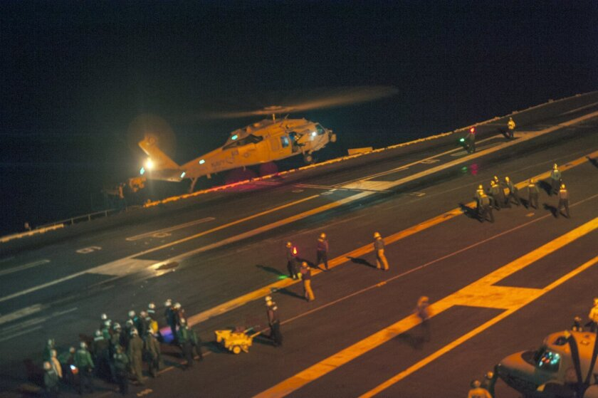 An MH-60S Sea Hawk helicopter lands on the flight deck of the USS Carl Vinson (CVN 70) during search and rescue operations for a missing pilot on Friday, Sept. 12, 2014. After two jets crashed in the western Pacific, one pilot was immediately rescued. A night search for the missing pilot was underway. The F/A-18C Hornet fighter jets were from Carrier Air Wing 17 based at Naval Air Station Lemoore in California's San Joaquin Valley. (US Navy, MCS 2nd Class John Philip Wagner, Jr., Released)