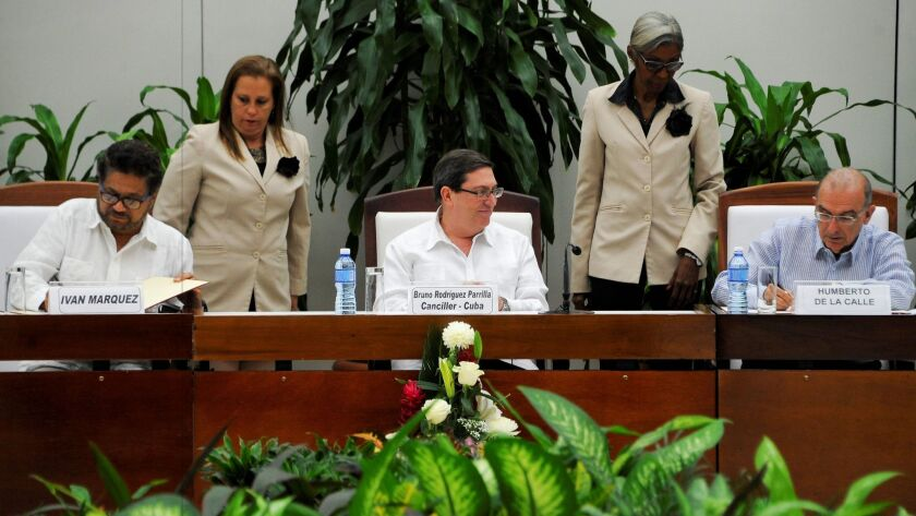 FARC commander Ivan Marquez, left, and Humberto de la Calle, head of the Colombian delegation for peace talks, sign a new agreement Saturday in Havana as Cuban Foreign Affairs Minister Bruno Rodriguez Parrilla looks on.