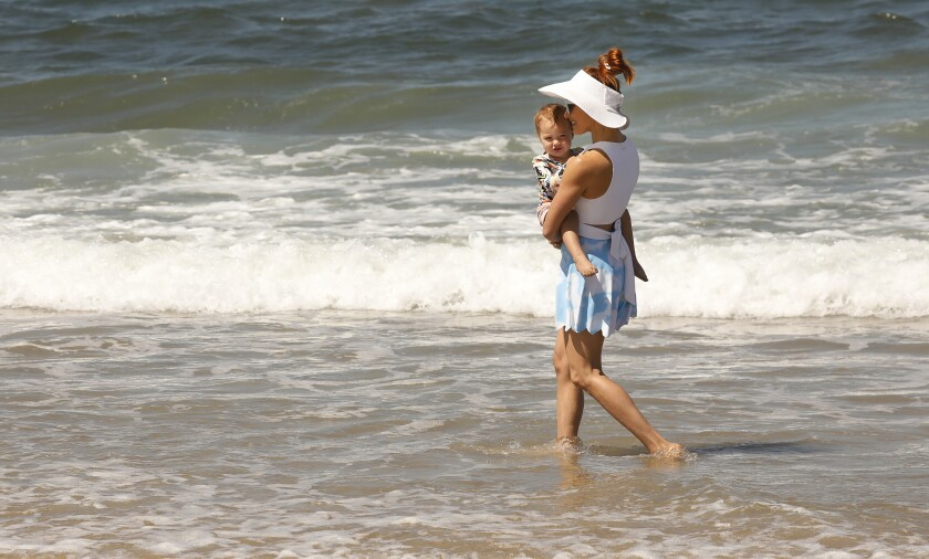 A woman plays with her 1-year-old daughter in the surf at Playa del Rey.
