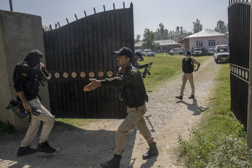 Indian police men arrive at a government school where two teachers were shot dead by assailants in the outskirts of Srinagar, Indian controlled Kashmir, Thursday, Oct. 7, 2021. Authorities blamed militants fighting against Indian rule for the attack. Thursday's incident marks the seventh targeted killings in six days. (AP Photo/Dar Yasin)