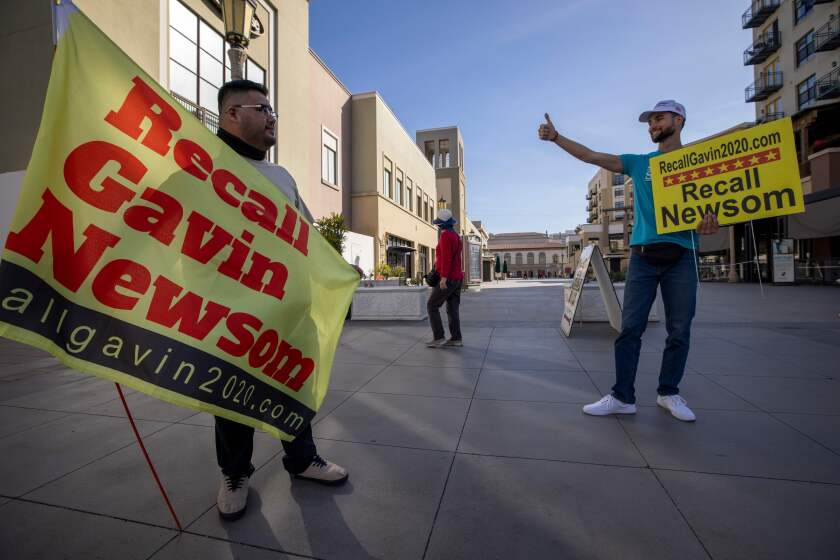 Two men with signs that say Recall Gavin Newsom