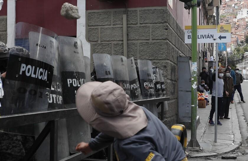 Un hombre lanza una piedra a la policía frente al palacio de gobierno durante una protesta en apoyo a los trabajadores de la salud en medio de la pandemia de COVID-19 en La Paz, Bolivia, el lunes 22 de febrero de 2021. Los trabajadores de la salud han convocado una huelga general para protestar contra una nueva ley sanitaria de emergencia que, entre otras cosas, permite la contratación de médicos extranjeros. (AP Foto/Juan Karita)
