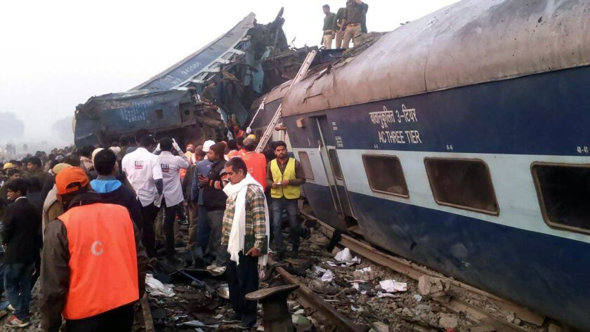 Rescue workers search derailed train cars near Pukhrayan, India.