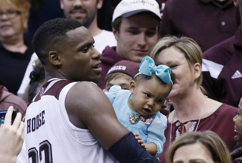 Texas A&M guard Danuel House holds his daughter, Ava Kennedy House in the stands after Texas A&M defeated Northern Iowa in double overtime of a second-round men's college basketball game in the NCAA Tournament Sunday, March 20, 2016, in Oklahoma City. Texas A&M won 92-88. (AP Photo/Sue Ogrocki)