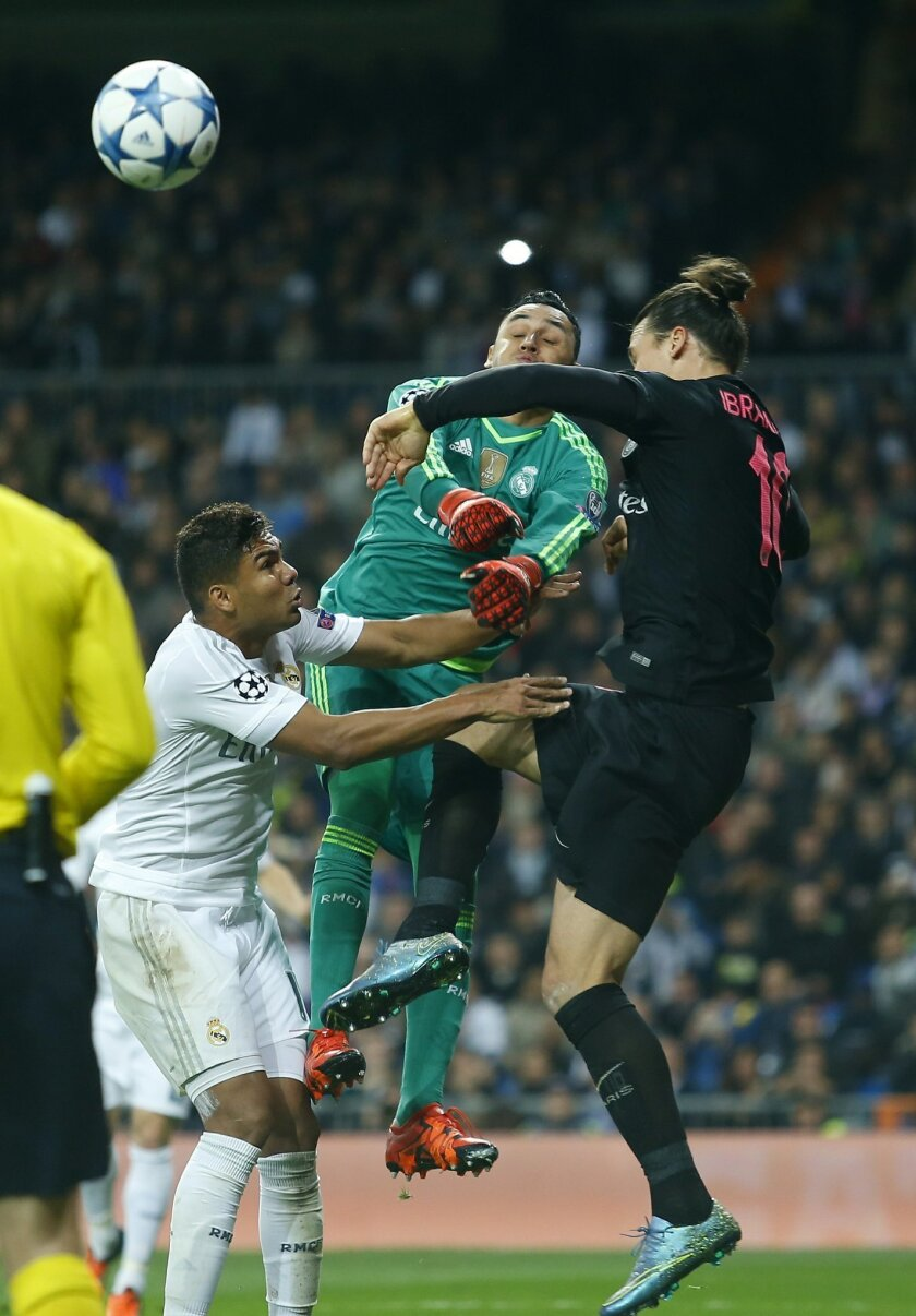Real Madrid's goalkeeper Keylor Navas, center, his teammate Henrique Casemiro, left, and PSG's Zlatan Ibrahimovic jump for the ball during the Champions League group A soccer match between Real Madrid and PSG at the Santiago Bernabeu stadium in Madrid, Tuesday, Nov. 3, 2015. (AP Photo/Francisco Sec