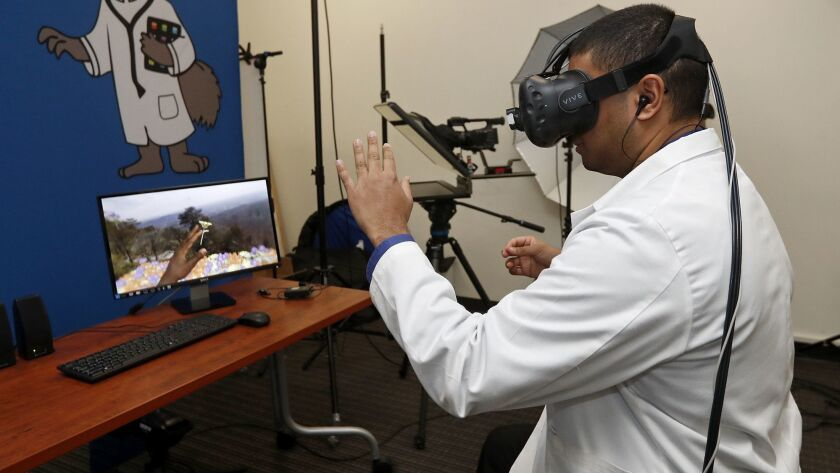 Mark Rupasinghe, a third-year UC Irvine medical student, demonstrates a virtual patient experience as part of the school's virtual reality program that helps caregivers better understand the plight of their patients.