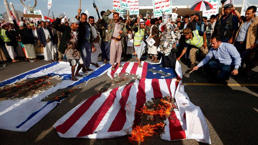 Supporters of Yemen's Houthi rebels burn U.S. and Israeli flags at a protest in Sana on May 20, the