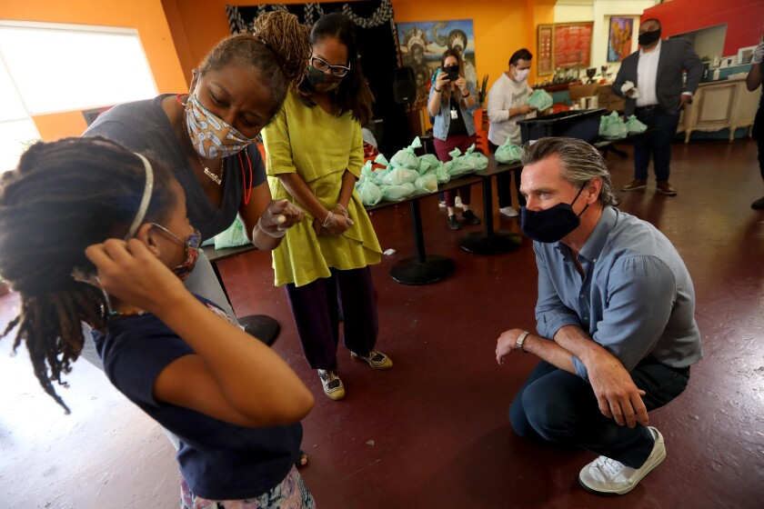 Gov. Gavin Newsom helps pack up lunches at Hot & Cool Cafe in Leimert Park