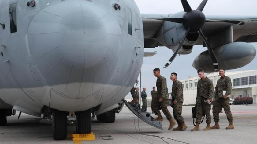 U.S. Marines board a KC-130J Hercules aircraft at Marine Corps Air Station Futenma on the Japanese island of Okinawa on Monday in preparation for a relief mission to the Philippines.