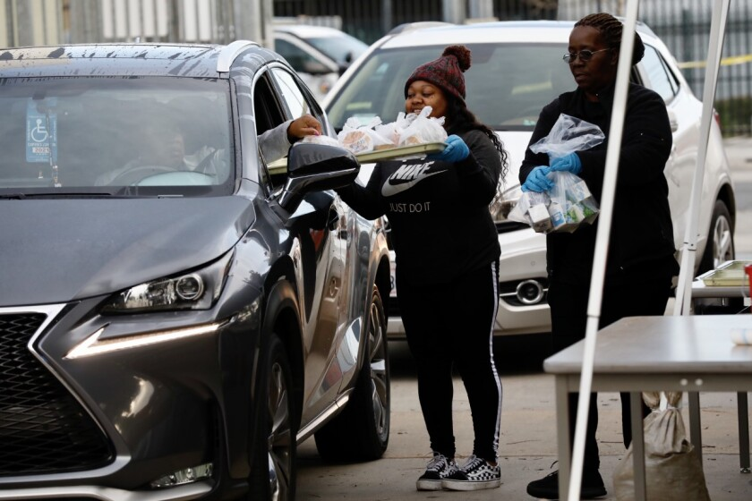 LAUSD volunteer Courtney Johnson delivers food to drivers at Dorsey High School.