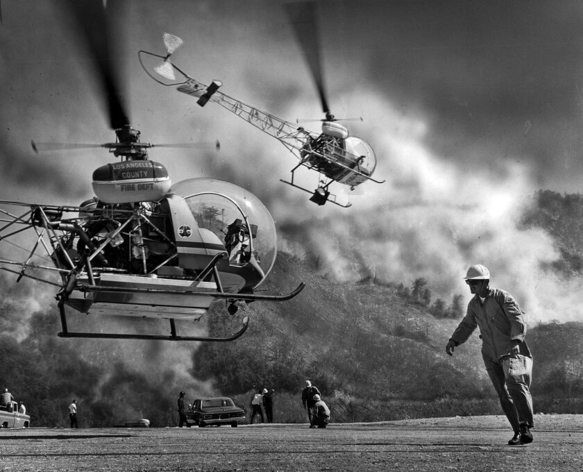 July 16, 1966: Los Angeles County firefighter Earl Wyat, right, directs a water-carrying helicopter off the ground as a brush fire spreads just off Angeles Crest Highway.