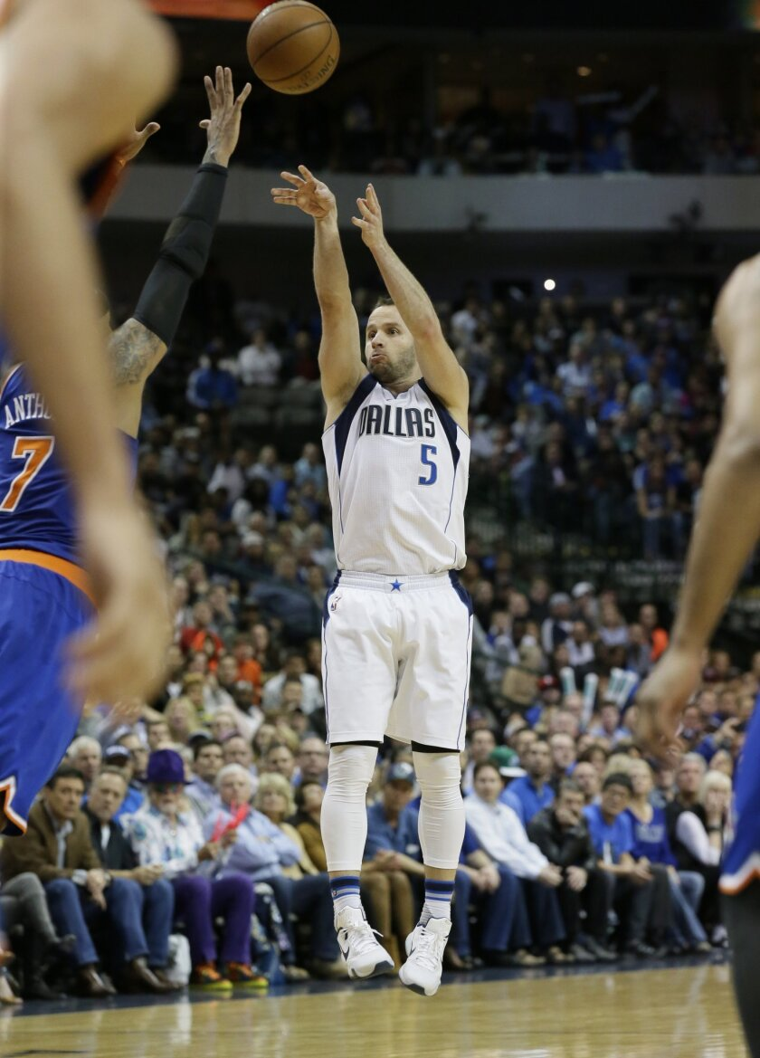 Dallas Mavericks guard J.J. Barea (5) hits a 3-point shot over New York Knicks forward Carmelo Anthony (7) during the fourth quarter of an NBA basketball game Wednesday, March 30, 2016, in Dallas. The Mavericks won 91-89. (AP Photo/LM Otero)