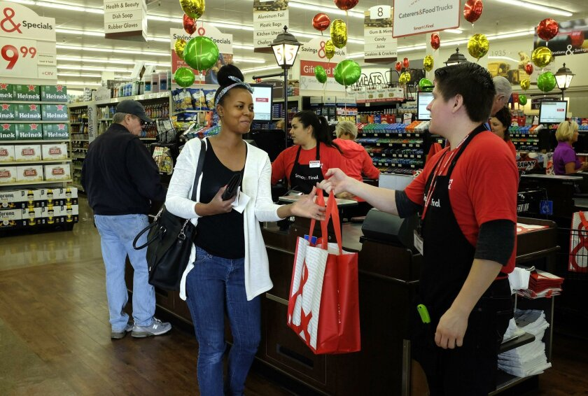 The new Smart & Final Extra in Coronado sits where a Haggen store used to be on the north side of the island not far from the ferry terminal.  Chantel McPherson, left, gets her purchases in a bag from cashier Andrew Guzman. McPherson works on base in Coronado. 