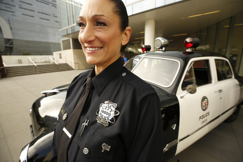 LAPD Officer Sara Faden wears her commemorative badge during an unveiling at police headquarters. She stands in front a vintage 1951 police cruiser.
