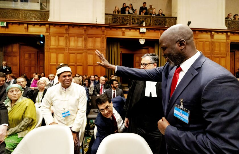 Aboubacarr Tambadou, Gambia's justice minister, waves to a representative of the Rohingya community Jan. 22 at the United Nations' International Court of Justice in The Hague.
