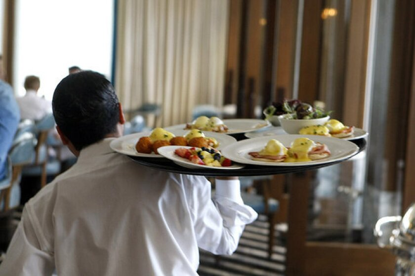 A waiter carries plated food to diners at Perle restaurant in Pasadena.