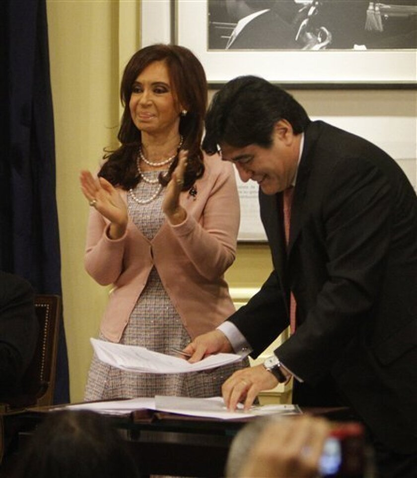Argentina's President Cristina Fernandez, left, applauds after signing the same sex marriage bill at the Latin America Patriots room of the government house in Buenos Aires, Wednesday, July 21, 2010. At right, Carlos Zanini, Argentina's Presidency legal aid.  (AP Photo/ Eduardo Di Baia)