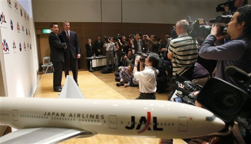 """Japan Airlines President Masaru Onishi, left, and American Airlines President Thomas Horton pose during a joint press conference in Tokyo Tuesday, Jan. 11, 2011. The heads of American Airlines and Japan Airlines said their beefed up alliance will give travelers cheaper fears, more routes and easier connections on flights across the Pacific. U.S. and Japanese regulators gave approval to the strengthened alliance late last year, which followed the two nations signing an """"open skies"""" deal to encourage air travel. (AP Photo/Shizuo Kambayashi)"""