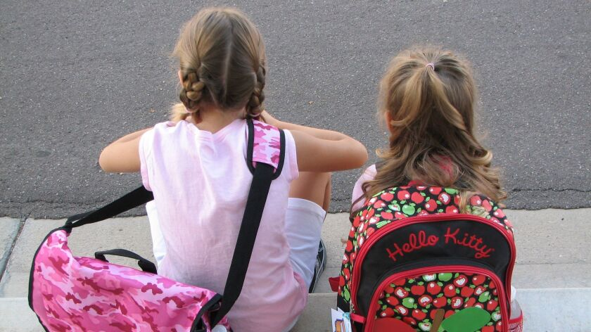 Two girls wait on the sidewalk on the first day of the school year on August 12, 2008.
