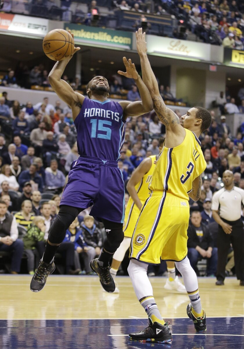 Charlotte Hornets' Kemba Walker (15) is fouled by Indiana Pacers' George Hill (3) as he goes up for a shot during the first half of an NBA basketball game Wednesday, Feb. 10, 2016, in Indianapolis. (AP Photo/Darron Cummings)
